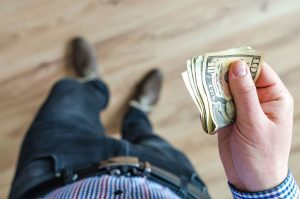 Can Family Law Courts Assign Income for Child or Spousal Support? This picture features a person looking down while holding money in their right hand.